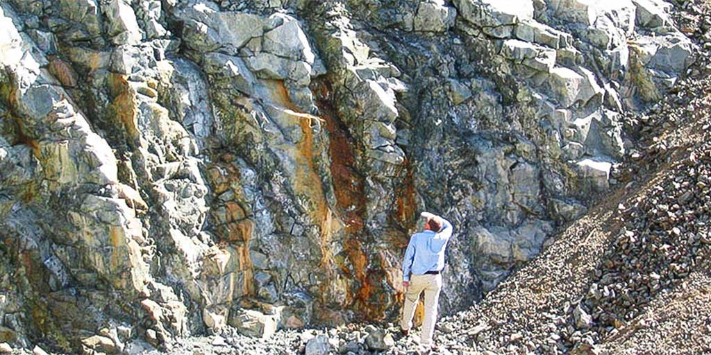 Man looking at geological strata for possible source of geomaterials